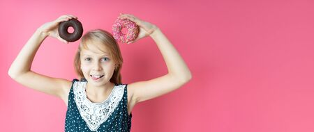 Funny happy girl with donut donuts on a pink background. Playful teenager girl holding donuts on her head. Woman shows a mouse ears. pink background Standard-Bild
