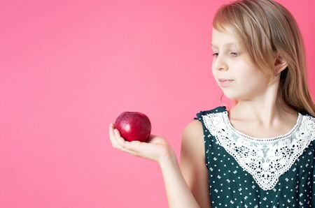 Portrait of happy girl with red apple isolated on pink background Standard-Bild