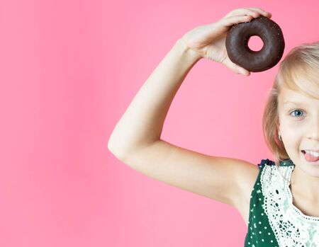 Funny happy girl with donut donuts on a pink background. Close-up portrait with a funny teen girl with a donut. Makes mouse ears out of sweetness