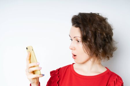 Cute brunette woman in a red sweater holding smartphone and smiling broadly, being joyful and excited after reading Surprised message in device, standing over white wall Standard-Bild