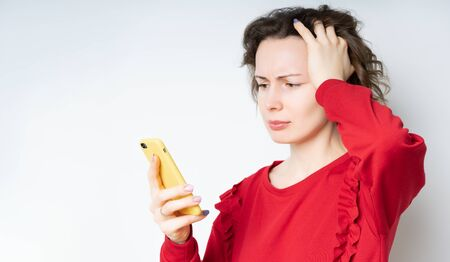 brunette young woman with a pleasant appearance looks with a frightened expression in a smartphone, reads shocking news on a web page, isolated on a light background. A woman holds on to her head Standard-Bild