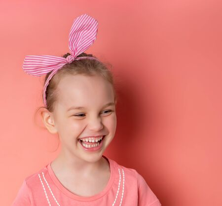 Little blonde girl in striped headband, dressed in blouse. She is laughing, posing against pink studio background. Happy childhood, fashion, advertising. Sincere emotions. Close up, copy space