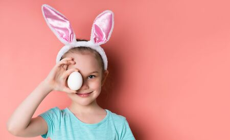 Little blonde girl in headband with rabbit ears, dressed in blue t-shirt. She is smiling, covered her eye with an egg, posing against pink background. Happy Easter, childhood. Close up, copy space Standard-Bild