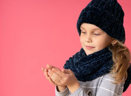 Happy toddler girl in a warm hat and scarf, having something in her hands, enjoying a miracle on a pink background.