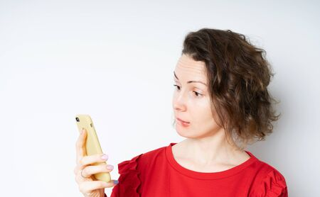 Surprised happy brunette woman in a red sweater holding smartphone and smiling broadly, being joyful and excited after reading message in device, standing over white wall