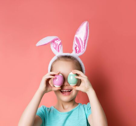 Little blonde kid in headband with bunny ears, dressed in blue t-shirt. She is laughing, covered her eyes with two colorful eggs, posing on pink background. Easter, childhood. Close up, copy space