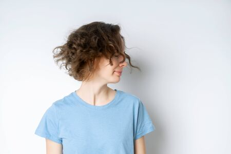 Happy beautiful young girl in a blue T-shirt shakes her head with her haircut on a white background