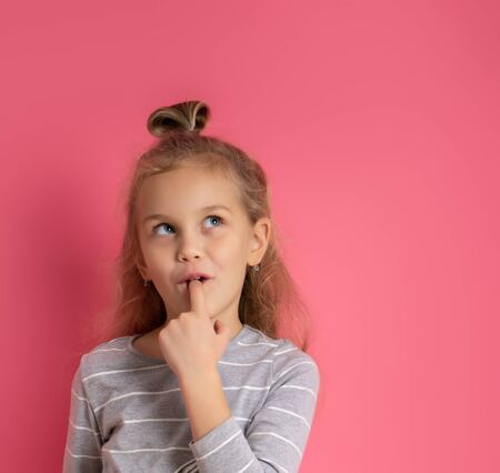 Little blonde girl with bun hairstyle, dressed in gray striped blouse. She put forefinger in mouth, looking thoughtful, posing on pink background. Childhood, fashion, advertising. Close up, copy space Standard-Bild
