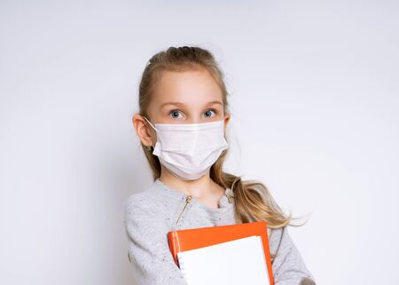 Blonde little kid in gray jumper and earrings. Holding notebooks. She is in medical mask, posing isolated on white. Coronavirus. Quarantine. Worldwide pandemic COVID-19. Close up, copy space Standard-Bild