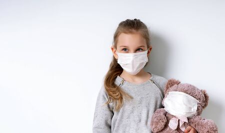 Blonde little model in gray jumper and medical mask, posing isolated on white. She holding toy teddy bear which is also in mask. Coronavirus. Quarantine. Pandemic COVID-19. Close up, copy space Standard-Bild