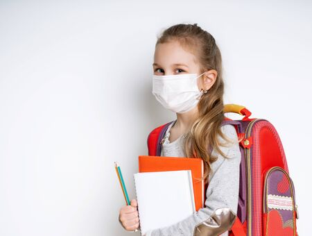 Blonde little girl in gray jumper, with colorful briefcase. Holding notebooks and two pencils. She is in medical mask, posing isolated on white. Coronavirus. Pandemic COVID-19. Close up, copy space
