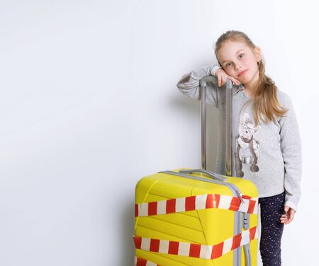 Blonde child in gray jumper posing isolated on white. She leaning on yellow suitcase tied by white and red warning tape. Coronavirus. Quarantine. Border closures, stop travelling, stay home. Close up