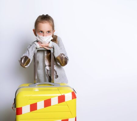Blonde kid in gray jumper, medical mask. Posing isolated on white. She leaning on yellow suitcase tied by white and red enclosing tape. Coronavirus. Border closures, stop travelling, stay home. Close up Standard-Bild