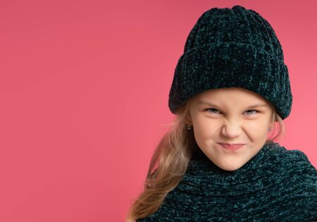 Little blonde kid dressed in green warm scarf and hat. She is smiling, looking naughty, posing against pink studio background. Childhood, fashion, advertising concept. Close up, copy space
