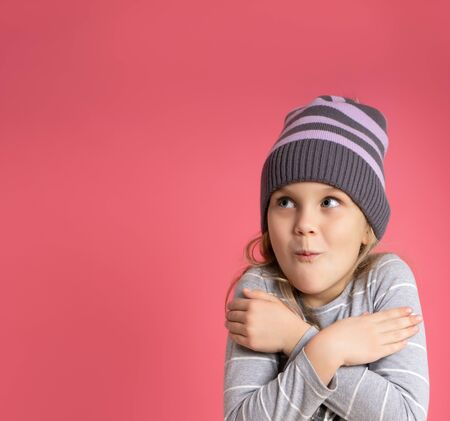 Little blonde girl dressed in gray striped blouse and hat. She hugging herself, looking frozen, posing against pink studio background. Childhood, fashion, advertising concept. Close up, copy space