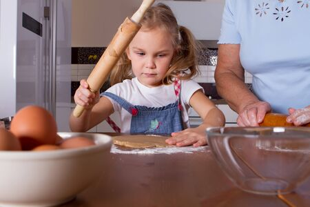 Little cute girl 4 years old helps grandmother to cook cookies. Rolls out the dough to cut with a tin. Home furnishings Standard-Bild
