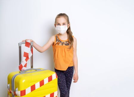 Blonde girl in casual wear holding a medical mask. Posing isolated on white. She is holding a yellow suitcase tied with a white and red warning tape. Closing borders, stop traveling, stay at home.