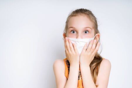 Blonde little girl in orange dress and medical mask, posing isolated on white. She is looking scared, touching her face. Coronavirus. Quarantine. Worldwide pandemic COVID-19. Close up, copy space Standard-Bild
