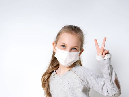 Blonde little girl in gray jumper and medical mask, posing isolated on white. She is looking at you and showing victory hand. Coronavirus. Quarantine. Worldwide pandemic COVID-19. Close up, copy space