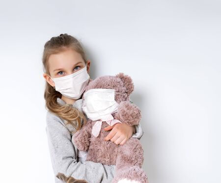 Blonde little female in gray jumper and medical mask, posing isolated on white. She hugging toy teddy bear which is also in mask. Coronavirus. Quarantine. Pandemic COVID-19. Close up, copy space