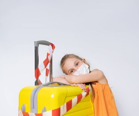 Blonde child in orange blouse, medical mask. Posing isolated on white. She leaning yellow suitcase tied white and red warning tape. Coronavirus. Border closures, stop travelling, stay home. Close up Standard-Bild
