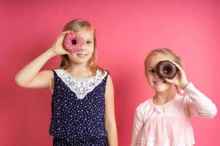 Two blonde girls in colorful dresses. They are smiling and looking through the holes of glazed donuts in their hands. Posing on pink studio background. Childhood, food concept. Close up, copy space