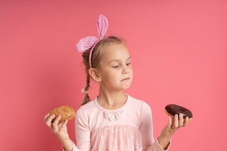 Little blonde model in dress, with striped headband and pigtail. She holding bun and chocolate donut in her hands. Posing against pink studio background. Childhood, food concept. Close up, copy space