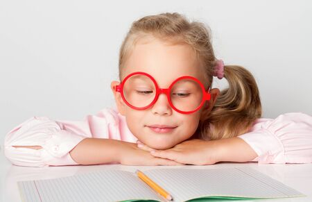 Little blonde kid with ponytail, in red framed glasses, pink blouse. She smiling, leaning on table with copybook and pencil on it. Posing isolated on white. Online education. Close up, copy space Standard-Bild