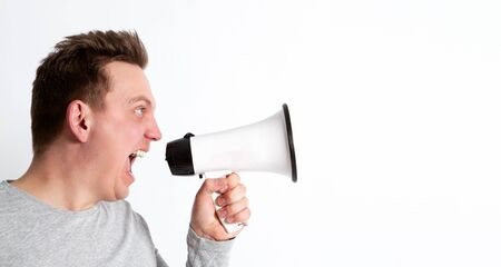 Close up portrait of a man shouting into a megaphone isolated on white. Copy space. Filmmaker, director, producer, cinematograph, camera, action, movie set, emotions, ordering, communication concept