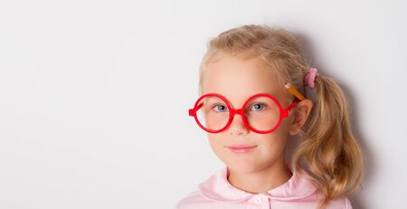 Little blonde child with ponytail, in red framed glasses, pink blouse. She is smiling, posing with yellow pencil behind her ear. Isolated on white. Childhood, online education. Close up, copy space Standard-Bild
