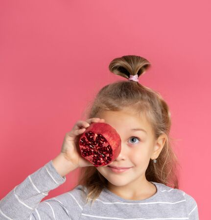 Smiling positive little girl in a gray sweater, holding a half pomegranate, closing one chapter, looking up at the advertisement, in high spirits, healthy eating, childrens menu, models on a pink studio background