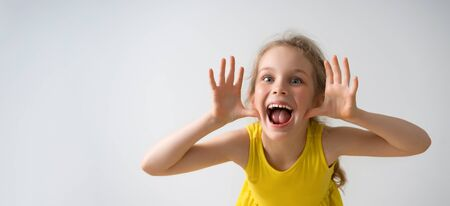 Sly happy preschool girl in sunny yellow dress teasing someone, yelling and laughing with funny face. Happy childhood, emotions, gesturing, playing, having fun. Close up studio shot isolated on white