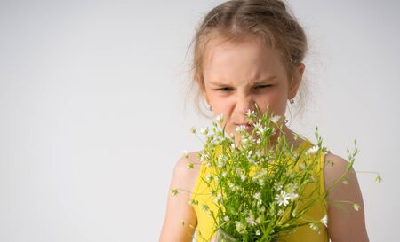Dissatisfied capricious little girl screwing up her face looking on a bouquet of field flowers in her hands. Children, gesturing and emotions, unhappy with a gift. Close up portrait isolated on white