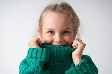 cute little girl hides her face under the thick collar of a warm knitted sweater. Children, gestures and emotions, happiness, winter. Close up studio shot isolated on white, copy space