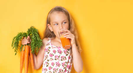 Pretty little girl in a gown with floral patteern drinking carrot juice holding bunch of carrots in hand. Waist up portrait isolated on yellow, copy space. Fashion for children, healthy food, summer