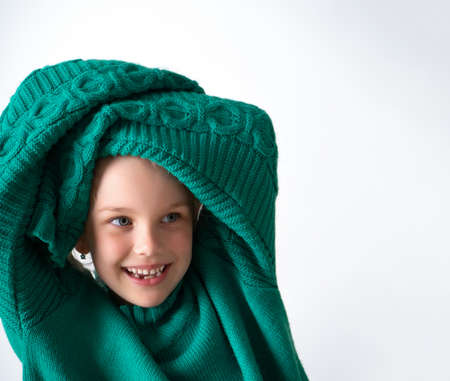 Playful little girl wearing knitted green sweater that is too big for her and raising hands in long sleeves above head. Happy childhood, facial expression, cute kids. Close up shot isolated on white. Фото со стока