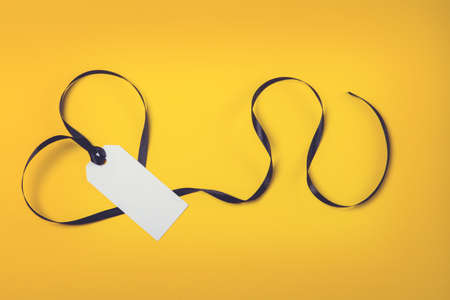 White tag with black ribbon on yellow background.