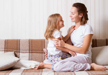 daughter and mother at home, sitting on the couch, wearing pajamas, hugging and laughing Standard-Bild