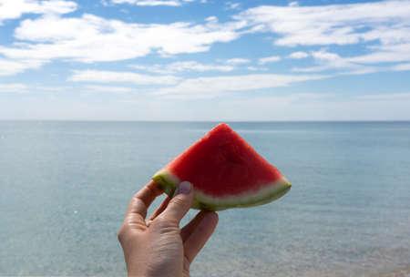 Hand holding slice of watermelon on the beach. Sea and blue sky background. Summer mood. Standard-Bild