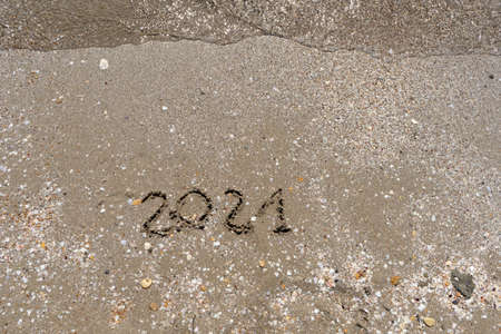 New Year 2021 is coming - inscription 2021 beach sand the wave water is starting to cover the digits - Summer beach holiday 2021 season golden sand old year - message handwritten - empty copy space