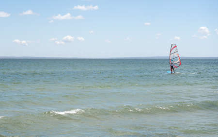Recreational Water Sports. Windsurfing. young sports guy is riding windsurfing (board with a sail) on the black sea.. Extreme Sport Action. Recreational Sporting Activity. Healthy Active Lifestyle. Summer Fun Adventure. Hobby