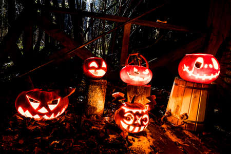 Scary Halloween pumpkins with eyes glowing inside on a black background, night street, holiday eve Standard-Bild