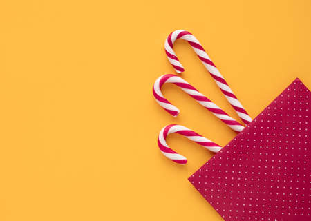 Christmas mint candies on yellow background with gift envelope, Christmas and holidays coming, time to give gifts