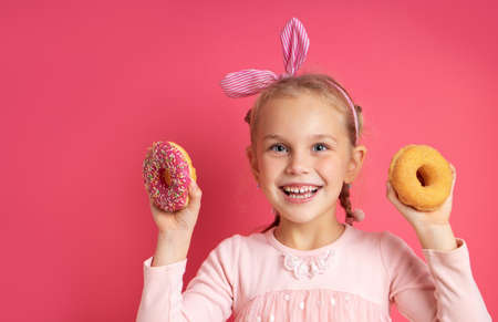 Portrait of a cheerful little girl with a funny headband having fun towards the camera with colorful donuts isolated on  pink
