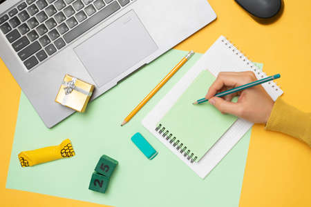 Workspace with a laptop, the hands of a girl writes a list of gifts in a notebook, a gift box and 25 on a yellow background. Layout of the apartment, ordering gifts online, top view. Standard-Bild