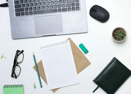 Modern white office desk with laptop, notepad and other supplies. Blank notepad page for entering text in the middle. Top view, flat lay