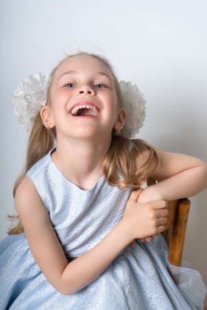 Portrait of a laughing girl with big bows for hair, sitting on a chair in a blue festive dress with hair with bows, on a light background. Retro style Standard-Bild