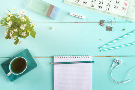 female flat lay on a blue background, top view of the desktop of a woman with flowers, pen, notepad and floral layout, August