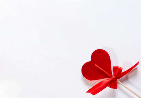 One sweet red lollipop heart with a bow for Valentines Day over light background with copy space. Located in a corner