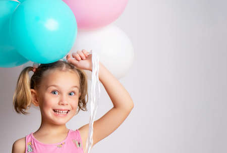 Little cute smiling 5 year old girl holding a bunch of colorful balloons. Standard-Bild